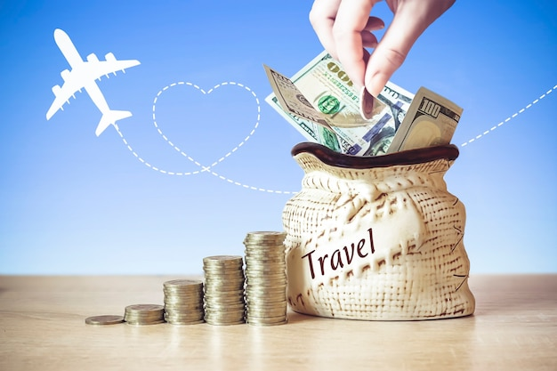 Dolary amerykańskie w torbie z monetami stos na stole, rozmycie tła z sylwetką samolotu. pojęcie podróży.