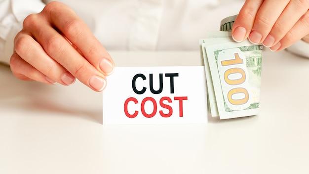 Dolary, biały notatnik na białej ścianie. cut cost tekst. koncepcja finansów i ekonomii. pojęcie finansów.