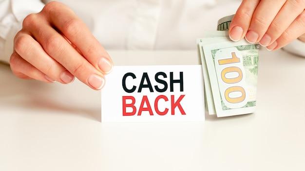 Dolary, biały notatnik na białej ścianie. tekst cash back. koncepcja finansów i ekonomii. pojęcie finansów.