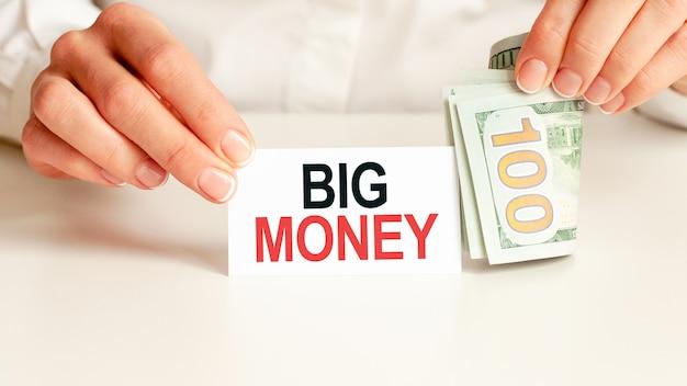 Dolary, biały notatnik na białej ścianie. tekst duże pieniądze. koncepcja finansów i ekonomii. pojęcie finansów.