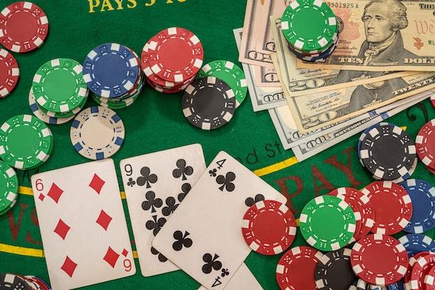 Dolary i karty do gry z żetonami w kasynie zielonym stole. hazard