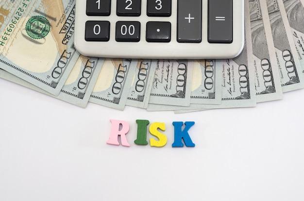 """Dolary, kalkulator i słowo """"ryzyko"""" ułożone z kolorowych liter na białym tle. pojęcie kryzysu gospodarczego, ryzyko biznesowe."""