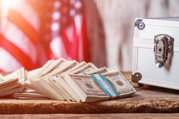 Dolary, sprawa i flaga usa. wiązki pieniędzy obok srebrnej skrzynki. biznes to potęga. wszystkie drogi są otwarte.