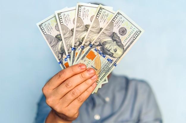 Dolary w rękach. biznesmen w niebieskiej koszuli trzyma 500 dolarów. fanem pieniędzy