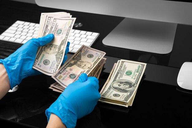 Dolary w ręku w niebieskich rękawiczkach medycznych. kryzys koronawirusowy. oszczędzać pieniądze.