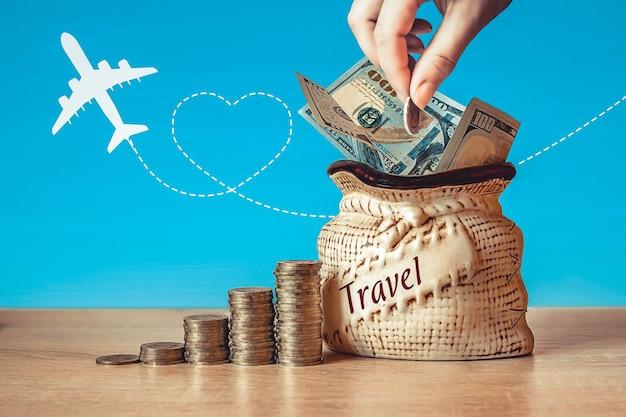 Dolary w torbie z monetami stos na stole, niebieskie tło z sylwetką samolotu. koncepcja oszczędzania pieniędzy na podróże.