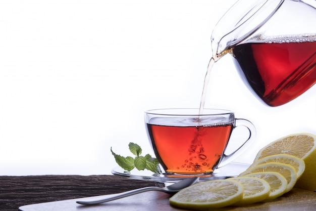 Dolewanie gorącą herbatę w filiżankę na białym tle