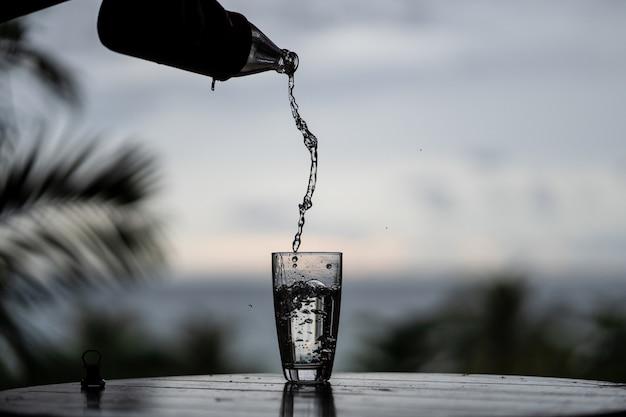 Dolewanie woda z butelki w szkle na natury tle