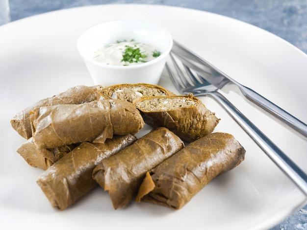Dolma na białym talerzu z sosem kefirowo-czosnkowym