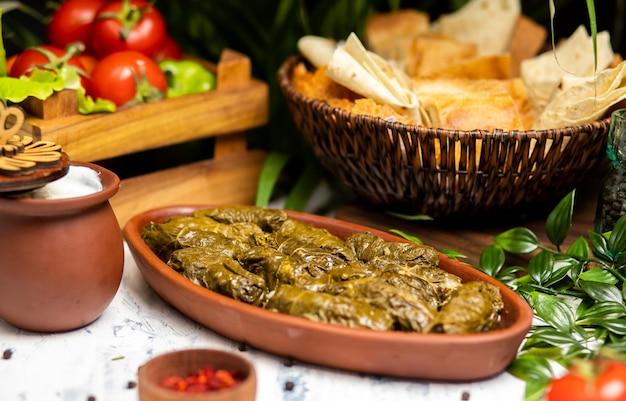 Dolma (tolma, sarma) - nadziewane liście winogron z ryżem i mięsem. na kuchennym stole z jogurtem, chlebem, warzywami. tradycyjna kuchnia kaukaska, turecka, turecka i grecka