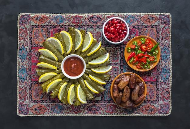 Dolma w liściach winogron z mięsem, ryżem i przyprawami na czarnym stole.