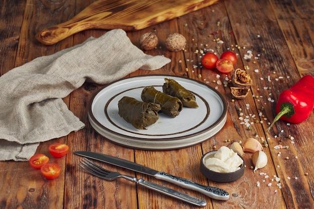 Dolma z mięsem - mięso mielone zawijane w liść winogronowy. kuchnia gruzińska na drewnianym stole.
