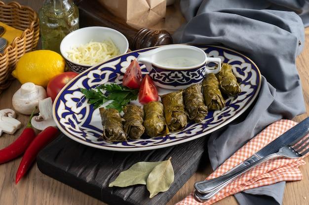 Dolma z warzywami i sosem koperkowym na talerzu z tradycyjnym uzbeckim