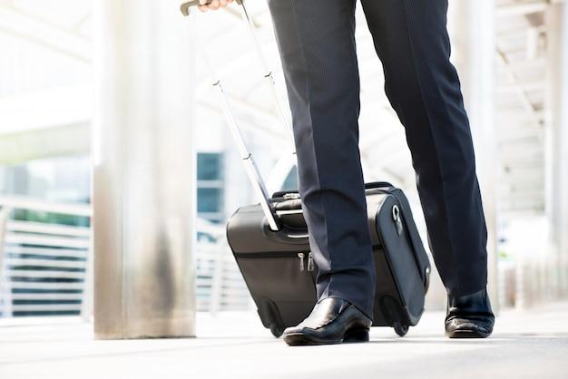 Dolna część podróżującego biznesmena chodzącego i ciągnącego bagaż