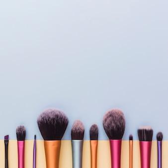 Dolna granica z pędzlem do makijażu na szarym tle