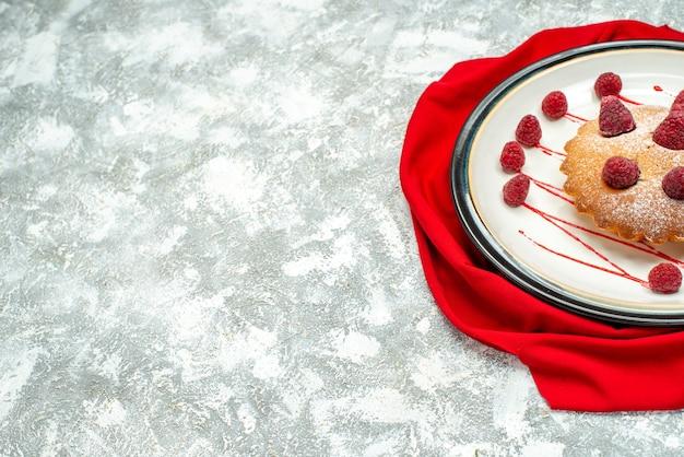 Dolna połowa tort jagodowy na białym owalnym talerzu czerwony szal na szarej powierzchni fre space