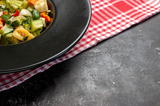 Dolna połowa widok zielona sałatka z pomidorów na owalnym talerzu widelec na ciemnym