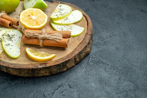 Dolna połowa widoku plasterki jabłka cynamon i plasterki cytryny na desce z suszonym jabłkiem w proszku miętowym na czarnym stole