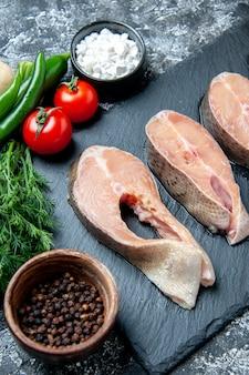 Dolna połowa widoku surowych plasterków ryb na czarnej tablicy na stole