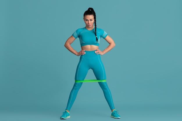 Dolnej części ciała. piękna młoda lekkoatletka praktykujących, monochromatyczny niebieski portret. sportowy fason brunetki z gumkami. koncepcja budowy ciała, zdrowego stylu życia, piękna i działania.