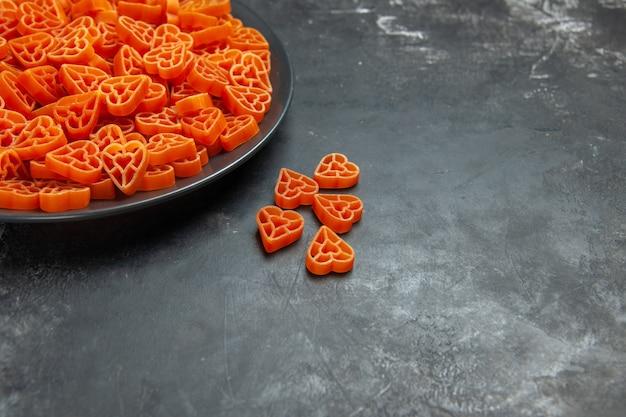 Dolny widok połowy czerwonego włoskiego makaronu w kształcie serca na czarnym owalnym talerzu na ciemnej powierzchni