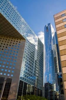 Dolny widok szklanych drapaczy chmur dzielnicy biznesowej paryża la defense przeciwko błękitne niebo pochmurne