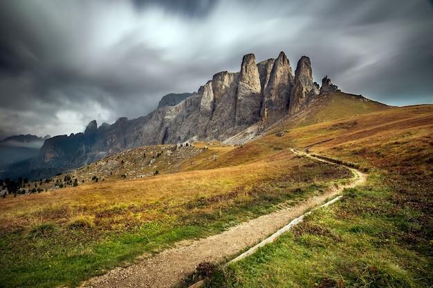 Dolomity w południowym tyrolu otoczone zielenią pod zachmurzonym niebem we włoszech