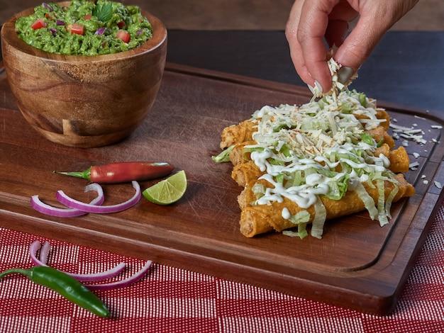 Dołożyłem ser do pysznych złocistych tacos, typowych meksykańskich potraw