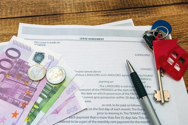 Dom, dom, nieruchomość, wynajem nieruchomości, umowa najmu z piórem, pieniędzmi, monetami, kluczami