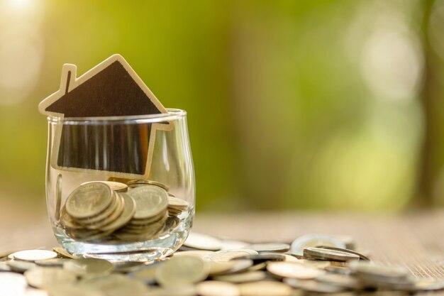 Dom drewniany model i monety stos na drewnianym stole. oszczędności finansowe na koncepcję domu