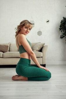 Dom fitness. piękna kobieta robi ćwiczenia w domu w salonie.
