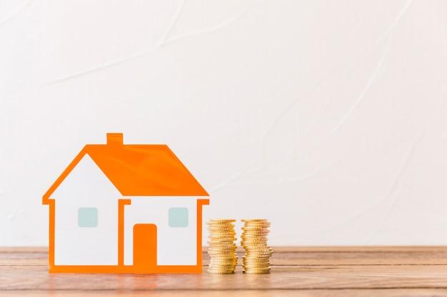 Dom i brogować monety na drewnianym stole