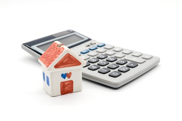 Dom i kalkulator na białym tle