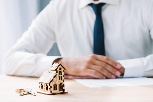 Dom i klucze w pobliżu agenta nieruchomości