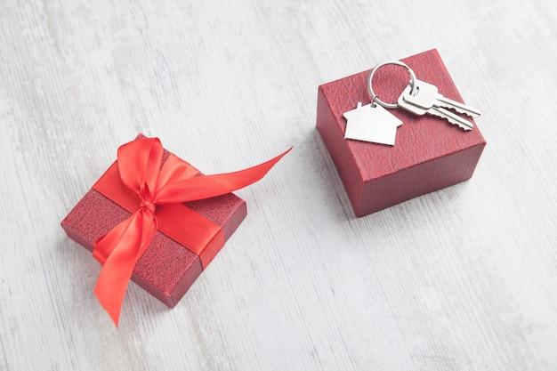 Dom i klucze z pudełkiem na białym tle.