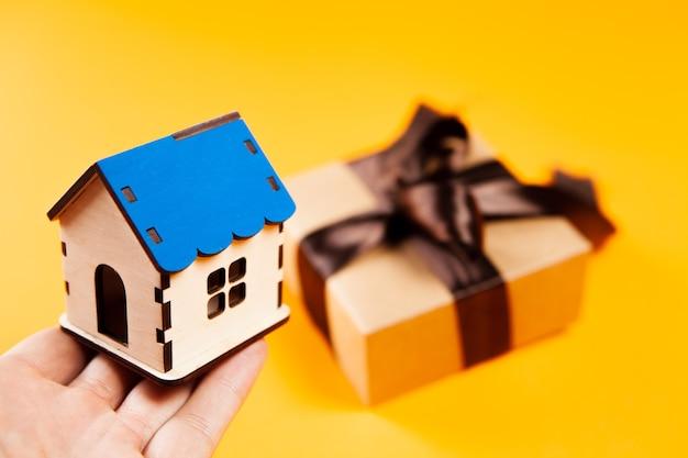 Dom i pudełko upominkowe na żółtej powierzchni
