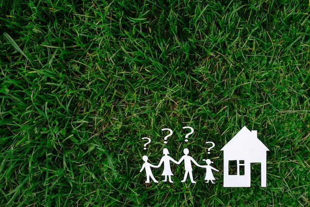 Dom i rodzina z wątpliwościami na tle trawy