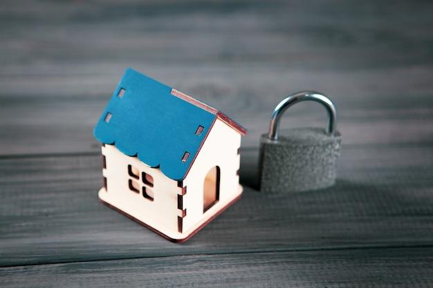 Dom i zamek na czarnej drewnianej powierzchni. koncepcja ochrony domu. blokada domu