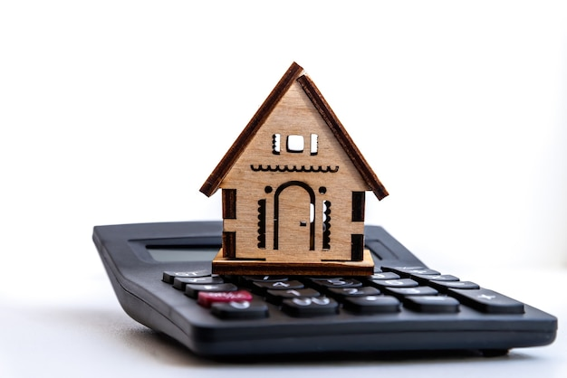 Dom jest umieszczony na kalkulatorze. planowanie oszczędności na zakup koncepcji domu na nieruchomości, hipoteki i inwestycje w nieruchomości.