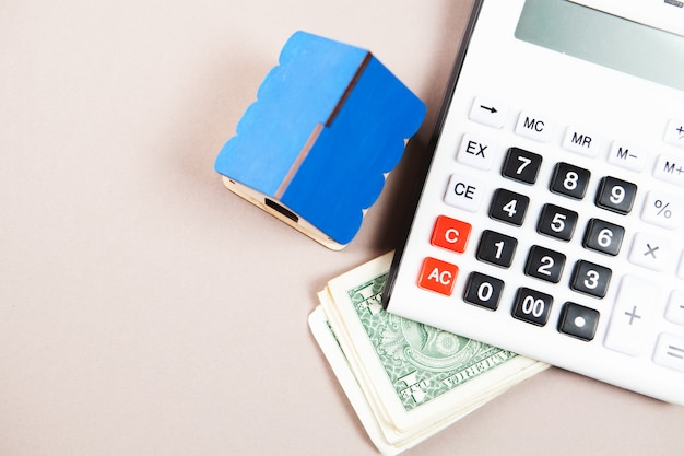 Dom, kalkulator i pieniądze na stole. koncepcja kalkulacji kosztu domu