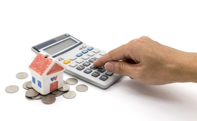 Dom, kalkulator i ręka na białym tle