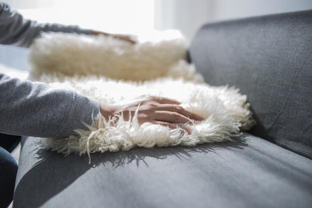 Dom, koncepcja nieruchomości i mebli - mężczyzna dekorowanie nowego domu - wprowadzenie dywanu owczego na kanapie