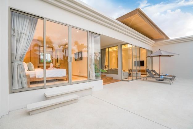 Dom lub dom projekt zewnętrzny pokazujący tropikalną willę przy basenie z leżakiem