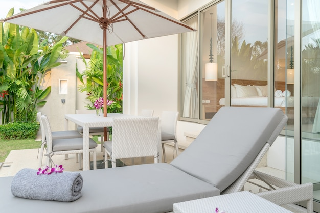 Dom lub dom projekt zewnętrzny pokazujący tropikalną willę przy basenie z łóżkiem do opalania, parasol