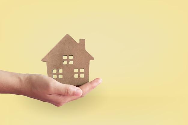 Dom lub model domu na ręce kobiety w pastelowych kolorach.