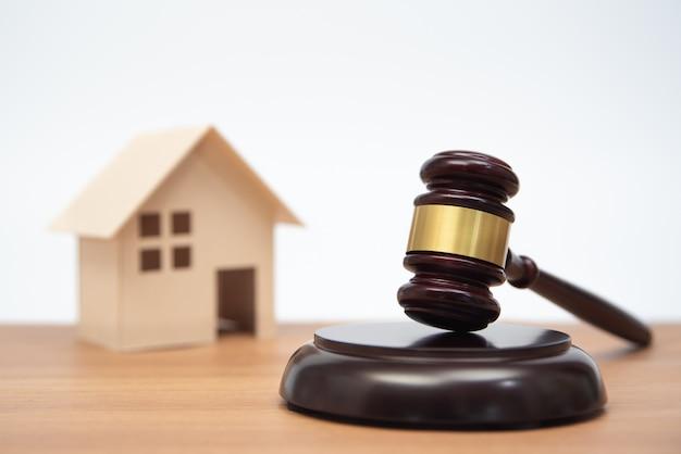 Dom miniatur na drewnianym stole i młotek sędziego.
