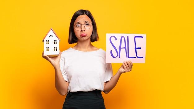 Dom młoda ładna kobieta dla koncepcji sprzedaży