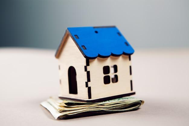 Dom na banknotach dolarowych na stole, koncepcja wydatków na dom