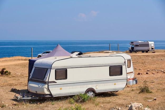 Dom na kółkach jest zaparkowany na plaży przed niebieskim morzem.