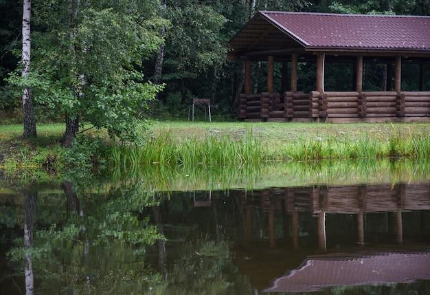 Dom na piknik nad jeziorem w lesie.
